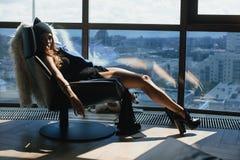 Συνεδρίαση γυναικών στην καρέκλα, τα πόδια της επάνω στο παράθυρο Στοκ φωτογραφίες με δικαίωμα ελεύθερης χρήσης
