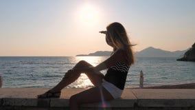 Συνεδρίαση γυναικών στην παραλία που εξετάζει την απόσταση με το χέρι του ματιού από τη The Sun φιλμ μικρού μήκους