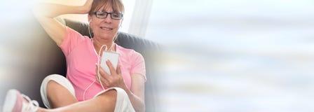 Συνεδρίαση γυναικών στον καναπέ και άκουσμα τη μουσική με το τηλέφωνο της Mobil της, ελαφριά επίδραση Στοκ Φωτογραφία