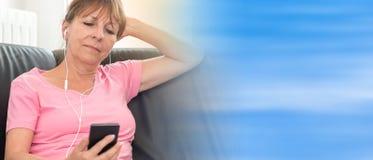Συνεδρίαση γυναικών στον καναπέ και άκουσμα τη μουσική με το τηλέφωνο της Mobil της, ελαφριά επίδραση Στοκ φωτογραφία με δικαίωμα ελεύθερης χρήσης
