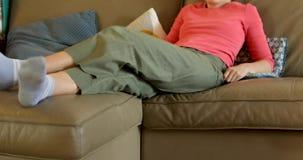 Συνεδρίαση γυναικών στον καναπέ και τον τηλεχειρισμό μετατροπής απόθεμα βίντεο