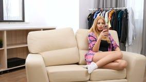 Συνεδρίαση γυναικών στον καναπέ στο σπίτι της που χρησιμοποιεί ένα smartphone φιλμ μικρού μήκους