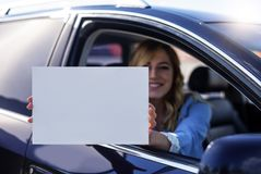 Συνεδρίαση γυναικών στο αυτοκίνητο και εκμετάλλευση μια άσπρη κενή αφίσα Στοκ Φωτογραφίες