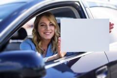 Συνεδρίαση γυναικών στο αυτοκίνητο και εκμετάλλευση μια άσπρη κενή αφίσα Στοκ Εικόνες