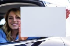 Συνεδρίαση γυναικών στο αυτοκίνητο και εκμετάλλευση μια άσπρη κενή αφίσα Στοκ φωτογραφίες με δικαίωμα ελεύθερης χρήσης