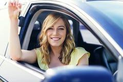Συνεδρίαση γυναικών στο αυτοκίνητο και εκμετάλλευση μια άσπρη κενή αφίσα Στοκ Φωτογραφία