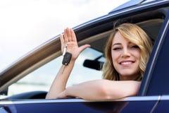 Συνεδρίαση γυναικών στο αυτοκίνητο και εκμετάλλευση μια άσπρη κενή αφίσα Στοκ εικόνες με δικαίωμα ελεύθερης χρήσης