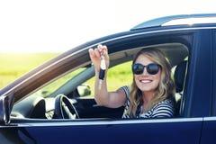 Συνεδρίαση γυναικών στο αυτοκίνητο και εκμετάλλευση μια άσπρη κενή αφίσα Στοκ φωτογραφία με δικαίωμα ελεύθερης χρήσης