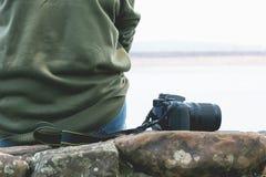 Συνεδρίαση γυναικών στο βράχο με τη κάμερα στο υπόβαθρο ποταμών Στοκ εικόνα με δικαίωμα ελεύθερης χρήσης