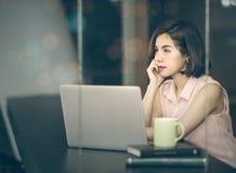 Συνεδρίαση γυναικών στο γραφείο και χρησιμοποίηση του lap-top κοιτάζοντας έξω Στοκ εικόνες με δικαίωμα ελεύθερης χρήσης