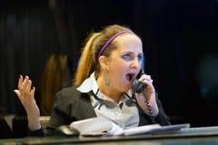 Συνεδρίαση γυναικών στο γραφείο της που λειτουργεί και που απαντά σε ένα τηλεφώνημα στοκ φωτογραφίες