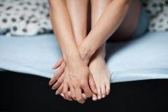 Συνεδρίαση γυναικών στο κρεβάτι που κρατά τα πόδια της στοκ εικόνες με δικαίωμα ελεύθερης χρήσης