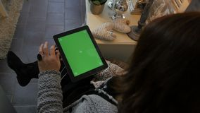 Συνεδρίαση γυναικών στο πάτωμα και χρησιμοποίηση του κάθετου υπολογιστή ταμπλετών με την πράσινη οθόνη Κλείστε αυξημένος των χερι φιλμ μικρού μήκους