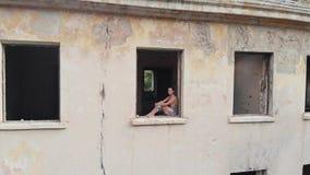Συνεδρίαση γυναικών στο παράθυρο στο εγκαταλειμμένο σπίτι απόθεμα βίντεο