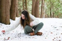 Συνεδρίαση γυναικών στο χιόνι που περιβάλλεται από τα φύλλα στοκ εικόνα με δικαίωμα ελεύθερης χρήσης
