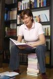 Συνεδρίαση γυναικών χαμόγελου ανώτερη στη στοίβα βιβλίων Στοκ εικόνες με δικαίωμα ελεύθερης χρήσης