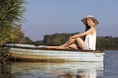 Συνεδρίαση γυναικών χαμόγελου νέα σε μια βάρκα το καλοκαίρι στοκ φωτογραφία