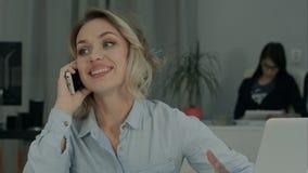Συνεδρίαση γυναικών χαμόγελου νέα στο γραφείο γραφείων και ομιλία στο τηλέφωνο κυττάρων Στοκ φωτογραφίες με δικαίωμα ελεύθερης χρήσης