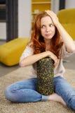 Συνεδρίαση γυναικών Displeased στο πάτωμα με τον κύλινδρο αφρού στοκ εικόνα με δικαίωμα ελεύθερης χρήσης