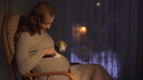 Συνεδρίαση εγκύων γυναικών στο λίκνισμα της καρέκλας στο σκοτεινό δωμάτιο Γυναικεία παιχνίδια με τις μικρές κάλτσες μωρών φιλμ μικρού μήκους