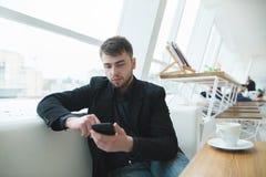 Συνεδρίαση επιχειρηματιών σε ένα παράθυρο εστιατορίων με ένα τηλέφωνο στα χέρια του Ένα άτομο γράφει ένα μήνυμα σε έναν καφέ Στοκ φωτογραφία με δικαίωμα ελεύθερης χρήσης