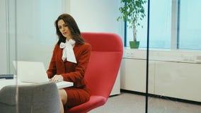 Συνεδρίαση επιχειρηματιών σε μια κόκκινη καρέκλα και εργασίες για τον υπολογιστή απόθεμα βίντεο