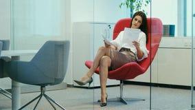 Συνεδρίαση επιχειρηματιών σε μια κόκκινη καρέκλα και τα έγγραφα ελέγχων απόθεμα βίντεο