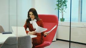 Συνεδρίαση επιχειρηματιών σε μια κόκκινη καρέκλα και τα έγγραφα ελέγχων φιλμ μικρού μήκους