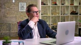 Συνεδρίαση επιχειρηματιών σκέψης καυκάσια στη θέση εργασίας του κοντά στο lap-top στον άσπρο υπολογιστή εσωτερικό απόθεμα βίντεο