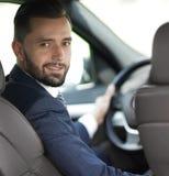 Συνεδρίαση επιχειρηματιών στη ρόδα ενός αυτοκινήτου και εξέταση τη κάμερα Στοκ Φωτογραφίες