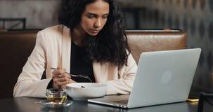 Συνεδρίαση επιχειρησιακών γυναικών με ένα lap-top στον καφέ και την κατανάλωση του γεύματος με ένα φλυτζάνι του τσαγιού στον πίνα απόθεμα βίντεο