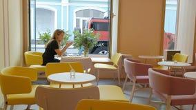 Συνεδρίαση επιχειρησιακών γυναικών σε έναν πίνακα σε έναν καφέ κατανάλωσης καφέδων και εργασία σε ένα lap-top φιλμ μικρού μήκους