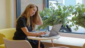 Συνεδρίαση επιχειρησιακών γυναικών σε έναν πίνακα σε έναν καφέ κατανάλωσης καφέδων και εργασία σε ένα lap-top απόθεμα βίντεο