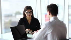 Συνεδρίαση εργαζομένων γραφείων στο στην αρχή χρησιμοποιώντας lap-top γραφείων, ενώ γυναίκες που μιλούν το τηλέφωνο στο υπόβαθρο φιλμ μικρού μήκους