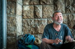 Συνεδρίαση ευτυχών και ατόμων χαμόγελου φτωχή άστεγη στη σκιά του κτηρίου στην αστική οδό στην πόλη στοκ εικόνα