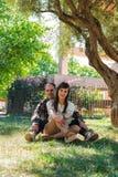 Συνεδρίαση ζευγών αγάπης στη χλόη στο πάρκο στοκ φωτογραφίες