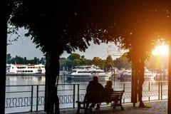 Συνεδρίαση ζευγών σκιαγραφιών από τη λίμνη Ιταλία, Arona τονισμός Εστίαση στους ανθρώπους που κάθονται στον πάγκο Στοκ εικόνες με δικαίωμα ελεύθερης χρήσης