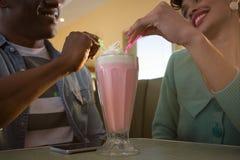 Συνεδρίαση ζευγών χαμόγελου στον καναπέ που έχει milkshake στο εστιατόριο στοκ εικόνες