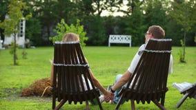 Συνεδρίαση ζεύγους στην πίσω αυλή ενός εξοχικού σπιτιού απόθεμα βίντεο