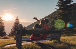 Συνεδρίαση ζεύγους στον πάγκο στα βουνά που προσέχουν το ηλιοβασίλεμα και που παίρνουν ένα selfie στοκ φωτογραφία