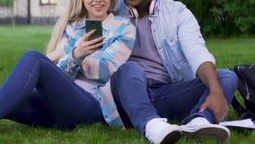 Συνεδρίαση ζεύγους στο χορτοτάπητα πολύ και εξετάζοντας το κινητό τηλέφωνο του κοριτσιού, συσκευές απόθεμα βίντεο