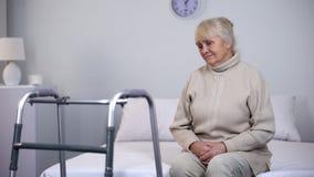 Συνεδρίαση ηλικιωμένων γυναικών που περπατά πλησίον το πλαίσιο, ανικανότητα μετά από την κοινή χειρουργική επέμβαση στοκ φωτογραφία με δικαίωμα ελεύθερης χρήσης