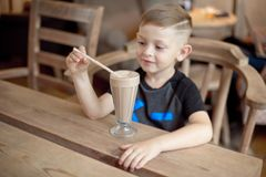 Συνεδρίαση κατανάλωσης μικρών παιδιών milkshake στον πίνακα στον καφέ Στοκ εικόνα με δικαίωμα ελεύθερης χρήσης