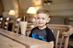 Συνεδρίαση κατανάλωσης μικρών παιδιών milkshake στον πίνακα στον καφέ Στοκ εικόνες με δικαίωμα ελεύθερης χρήσης