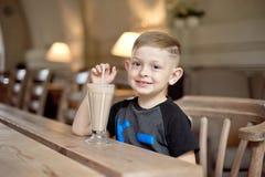 Συνεδρίαση κατανάλωσης μικρών παιδιών milkshake στον πίνακα στον καφέ Στοκ Εικόνες