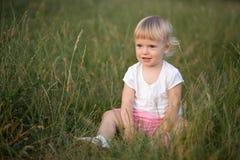 Συνεδρίαση κοριτσάκι στη χλόη Στοκ Φωτογραφία