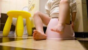Συνεδρίαση κοριτσάκι στο chamberpot Πόδια παιδιών Ένα μικρό παιδί μαθαίνει να πηγαίνει στο δοχείο, κινηματογράφηση σε πρώτο πλάνο φιλμ μικρού μήκους