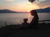 Συνεδρίαση κοριτσιών και σκυλιών δίπλα στην αδριατική θάλασσα Στοκ εικόνες με δικαίωμα ελεύθερης χρήσης