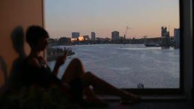 Συνεδρίαση κοριτσιών κοντά στο παράθυρο στο υπόβαθρο της πόλης και της θάλασσας απόθεμα βίντεο