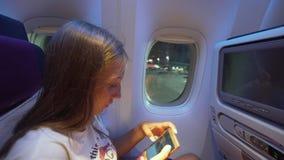Συνεδρίαση κοριτσιών με τηλέφωνο αεροσκαφών windowwith φιλμ μικρού μήκους